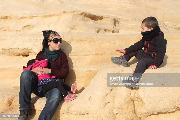 Mother breastfeeding her child while talking to his son