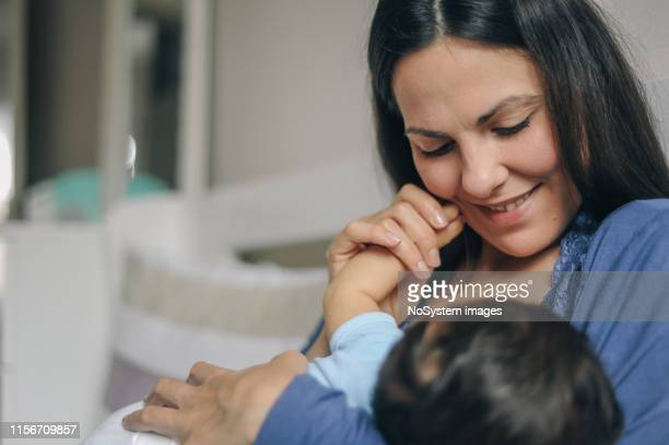 mother breastfeeding her newborn baby boy - adult breastfeeding stock pictures, royalty-free photos & images