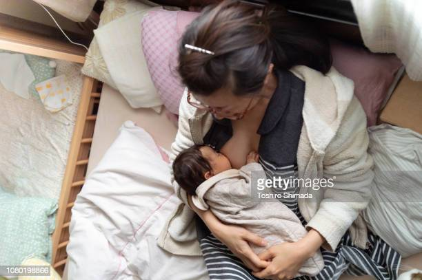 a mother breast-feeding on the bed - japanese breastfeeding stock pictures, royalty-free photos & images