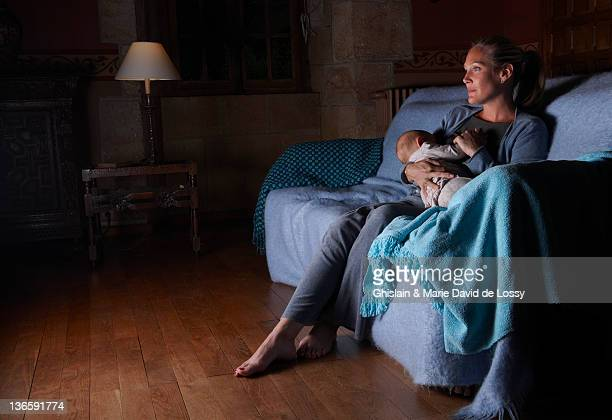mother breastfeeding with television - night stockfoto's en -beelden