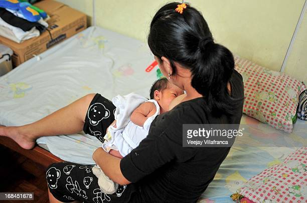 A mother breastfeeds her 2week old child at Nazareth House before Mother's Day this Sunday on May 10 2013 in Manila Philippines The Nazareth home...