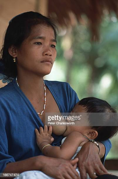 A mother breastfeeds her baby sitting outside her simple beachside hut on Siberut Island Due to the heavy prevalence of malaria pneumonia cholera and...