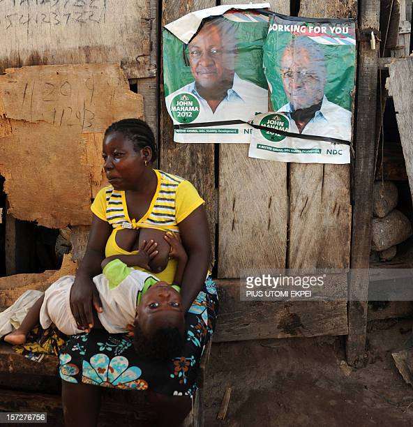 A mother breastfeeds her child backing posters of the presidential candidate of the ruling National Democratic Congress President John Mahama at...