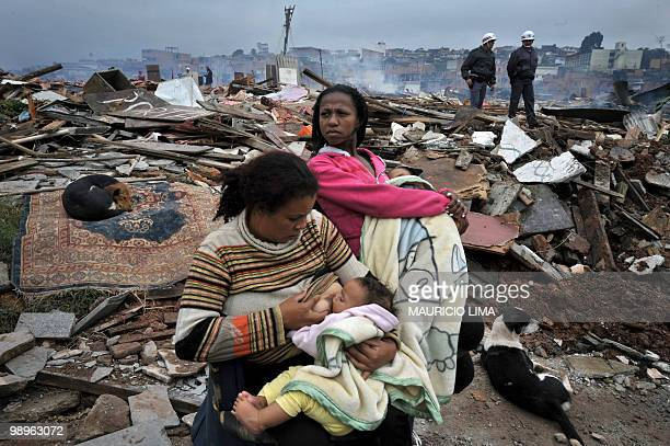 A mother breastfeeds her child next to rubble after her hut was demolished during an eviction at Capao Redondo shantytown southern outskirts of Sao...