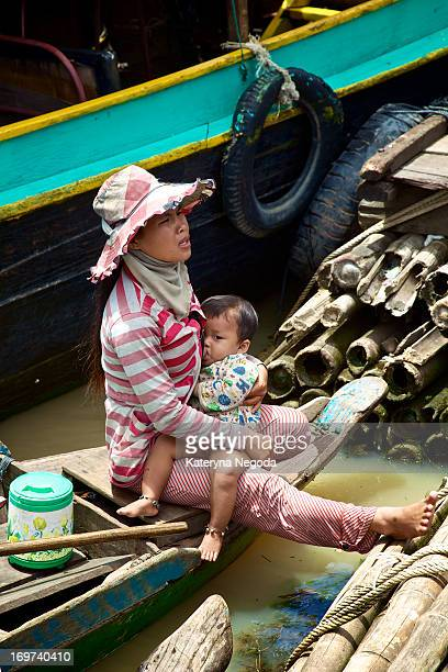 CONTENT] A mother breastfeeds her son and asks a dollar from tourists in Tonle Sap floating village Cambodia