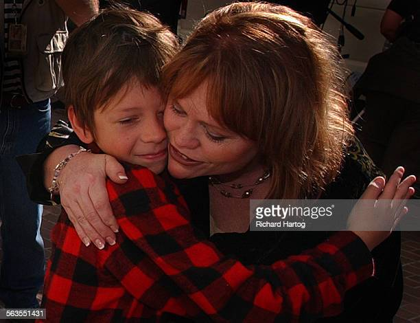 Mother Brenda van Dam, right, enjoys a tender moment as she gets a warm hug from eight–year–old Conner Linsley of San Diego just outside the Hall of...