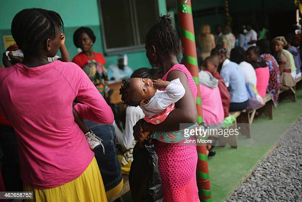 A mother brings her sick child for treatment at Redemption Hospital formerly an Ebola holding center on February 2 2015 in Monrovia Liberia Life is...