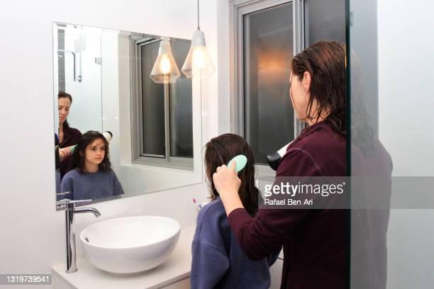 mother brushing and drying daughters hair in home bathroom - rafael ben ari stockfoto's en -beelden