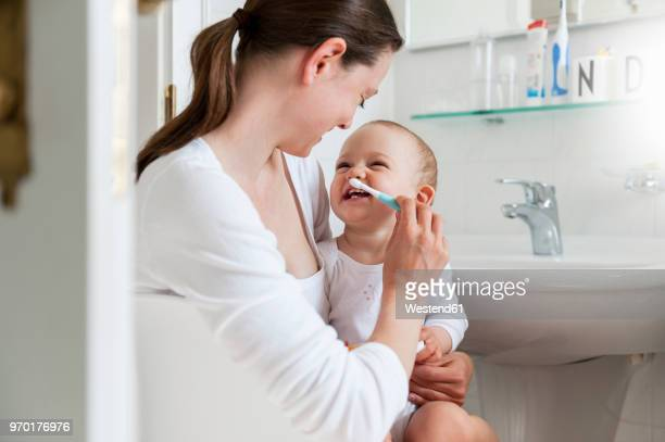 mother brushing baby's teeth in bathroom - 1歳以上2歳未満 ストックフォトと画像