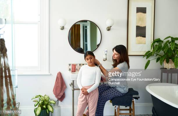 mother brushing daughter's hair in bathroom - photography stock pictures, royalty-free photos & images