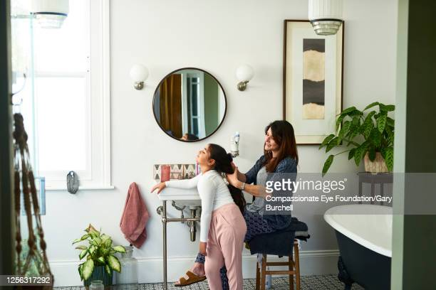 mother brushing daughter's hair in bathroom - toilet planter stock pictures, royalty-free photos & images