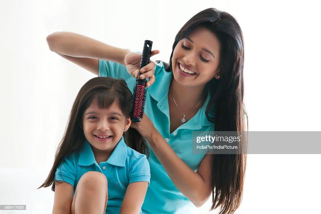 Mother brushing daughters hair : Stock Photo