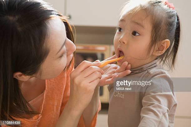 Mother Brushing Daughter's Teeth