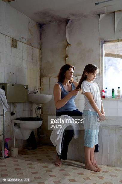 Mother brushing girls hair in bathroom
