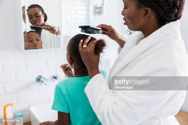 Mother brushing her daughters hair.
