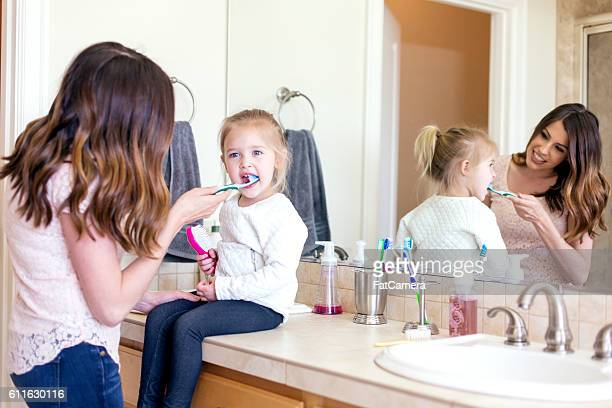 Mother brushing her daughters teeth as she sits on sink