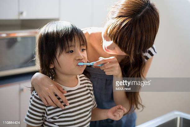 Mother Brushing Son's Teeth