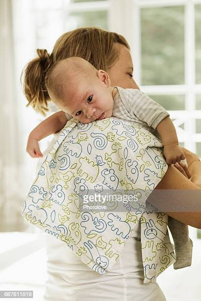 Mother burping baby son whilst carrying him on her shoulder
