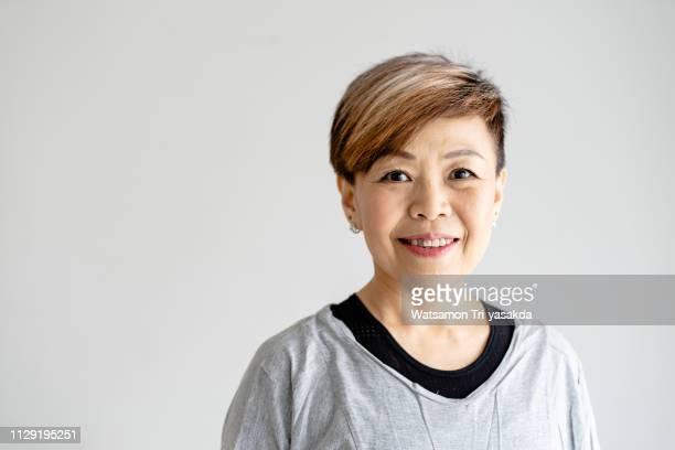 thai middle-aged woman enjoys yoga at home - タイ人 ストックフォトと画像