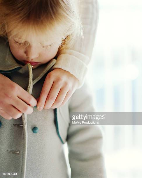 mother buttoning daughter's jacket - overcoat stock pictures, royalty-free photos & images