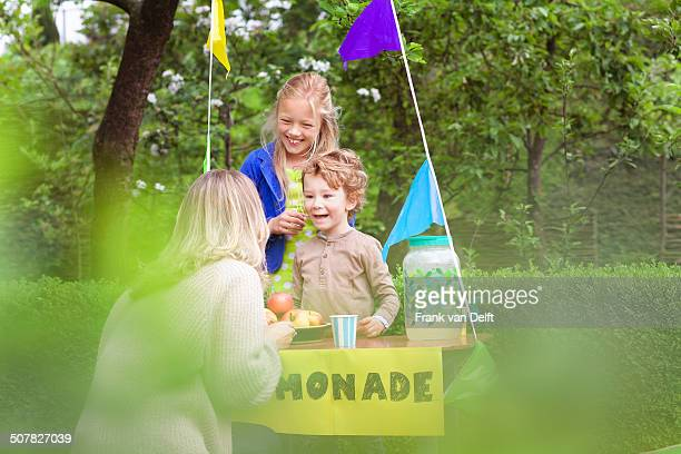 Mother buying lemonade from daughter's stand
