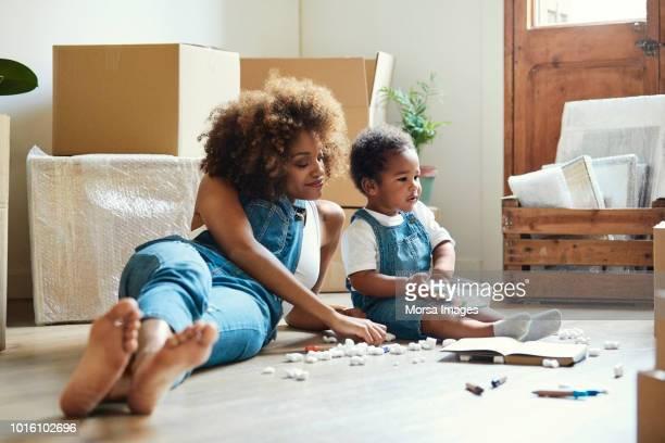 moeder van meisje met kleurpotloden in nieuw huis - afro amerikaanse etniciteit stockfoto's en -beelden