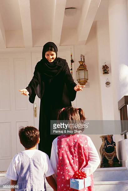 A mother calling her children affectionately as daughter hides the Gift from her.