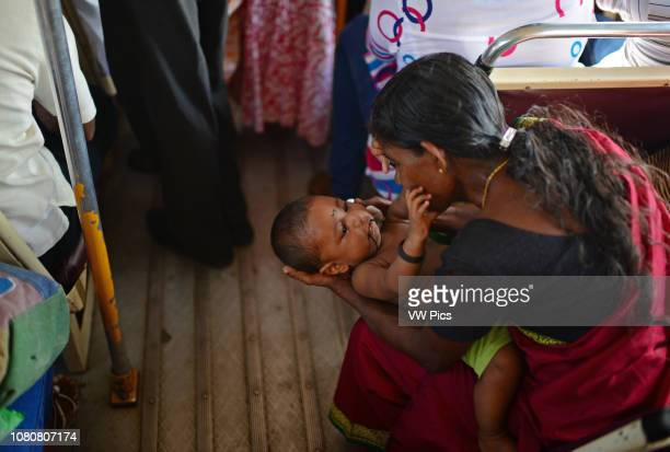 Mother calms a baby inside a public bus Sri Lanka