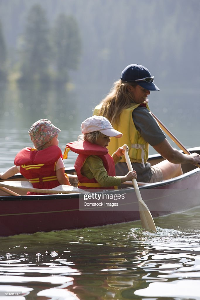 Mother canoeing with children : Stockfoto