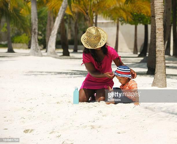 Mother/ Carer Putting Sunhat On Toddler