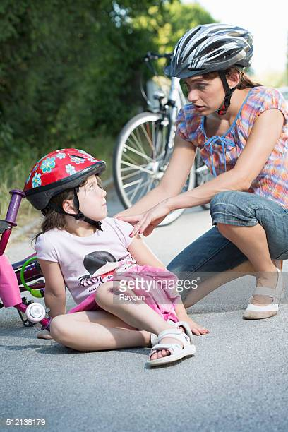 Mother caring for daughter fallen off bicycle