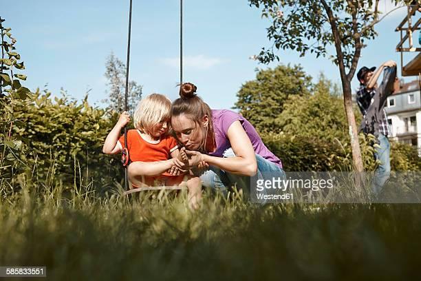 mother caring for injured daughter in garden - verletzung stock-fotos und bilder