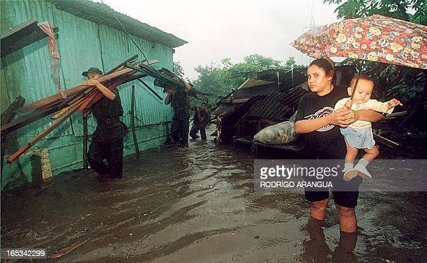 A mother carries her baby as she watch members of the army clean up after hurricane Mitch in a neighborhood in Managua Nicaragua 30 October 1998...