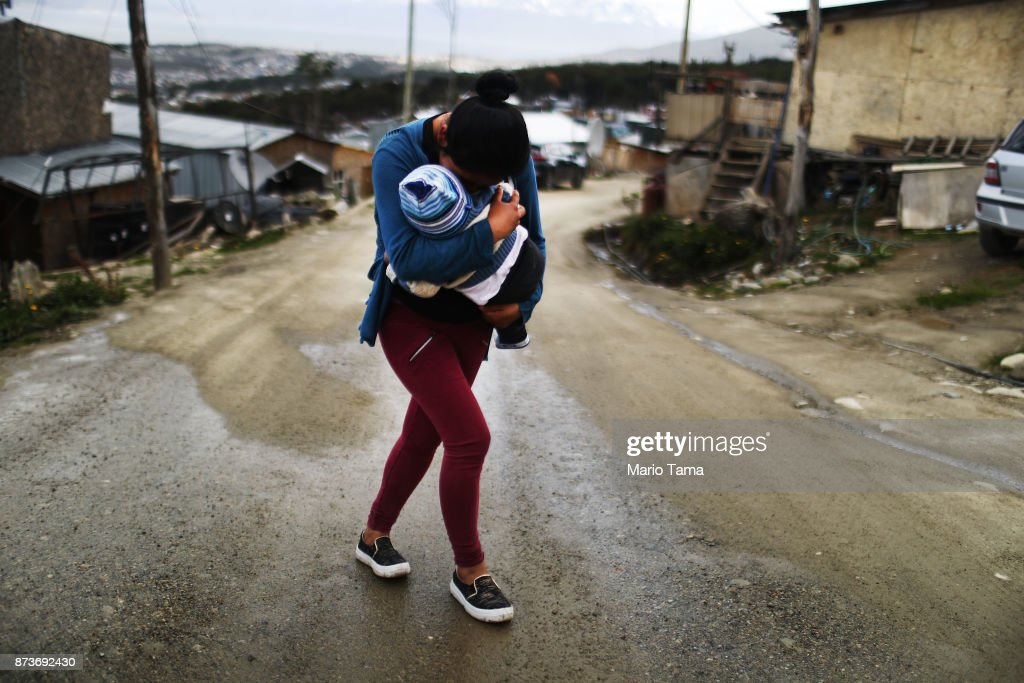 A mother carries her child in an informal mountainside community, whose residents depend on runoff water from snow and the receding Martial Glacier, on November 7, 2017 in Ushuaia, Argentina. Many Ushuaians have constructed homes in informal settlements due to a population boom and lack of affordable housing available. Ushuaia is situated along the southern edge of Tierra del Fuego, in the Patagonia region, and is commonly known as the 'southernmost city in the world'. The city's main fresh water supply comes from the retreating Martial Glacier, which may be at risk of disappearing. In a 2015 report, warming temperatures led to the loss of 20 percent of the mass and surface of glaciers in Argentina over the previous 50 years, according to Argentina's Institute of Nivology, Glaciology and Environmental Sciences (IANIGLIA). Ushuaia and surrounding Tierra del Fuego face other environmental challenges including a population boom leading to housing challenges following an incentivized program attracting workers from around Argentina. Population in the region increased 11-fold between 1970 and 2015 to around 150,000. An influx of cruise ship tourists and crew, many on their way to Antarctica, has also led to increased waste and pollution in the area sometimes referred to as 'the end of the world'.
