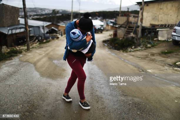 A mother carries her child in an informal mountainside community whose residents depend on runoff water from snow and the receding Martial Glacier on...