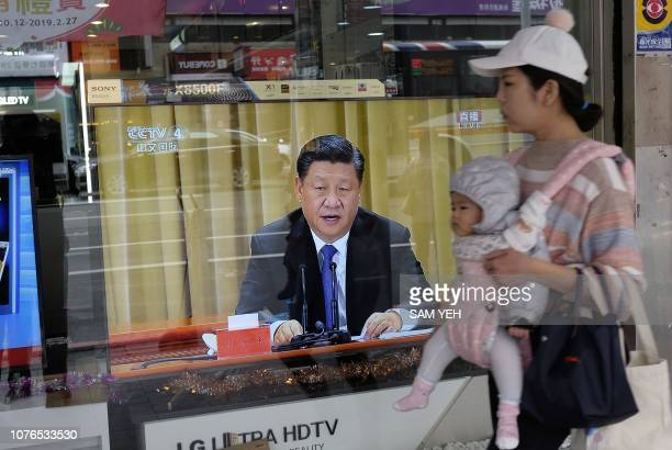 TOPSHOT A mother carries her child past a television in New Taipei City on January 2 2019 showing China's leader Xi Jinping making a speech...