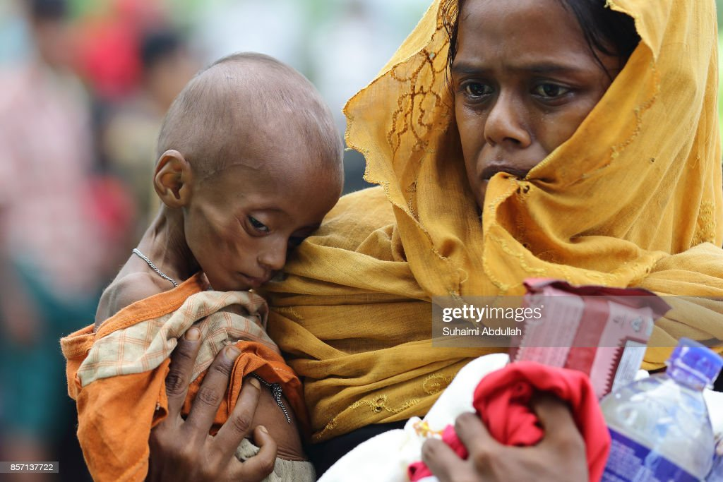 A mother carries her child to collect food supplies at the distribution point for food centre on October 2, 2017 in Kutupalong, Cox's Bazar, Bangladesh. Over 430,000 Rohingya refugees have fled into Bangladesh since late August during the outbreak of violence in Rakhine state as Myanmar's de facto leader Aung San Suu Kyi downplayed the crisis and defended the security forces while criticism on her handling of the Rohingya crisis grows. UN refugee chief Filippo Grandi has called on the Myanmar authorities to halt the violence.