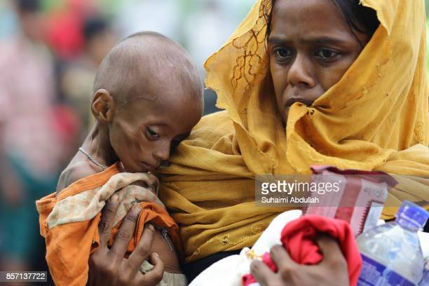 A mother carries her child to collect food supplies at the distribution point for food centre on October 2 2017 in Kutupalong Cox's Bazar Bangladesh...