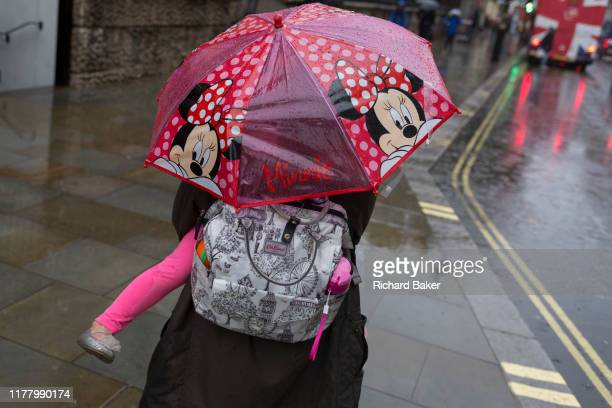 Mother carries her child under a Minnie Mouse umbrella during heavy rainfall on an autumn afternoon near Trafalgar Square, on 24th October 2019, in...