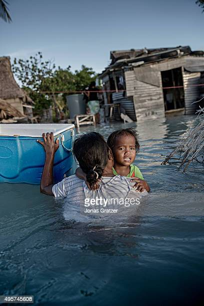 A mother carries her daughter as they wade through the sea water that has flooded their village The people of Kiribati are under pressure to relocate...