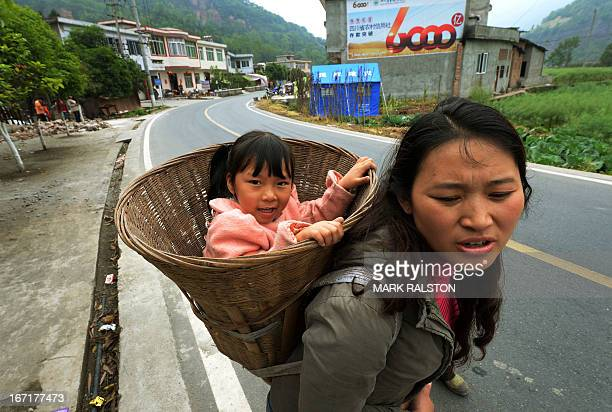 A mother carries her daughter in a basket as they walk to food distribution center near Longmen village after a magnitude 70 earthquake hit Lushan...