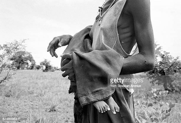 A mother carries her dead baby into the bush for burial at Ajiep southern Sudan during the height of the famine in