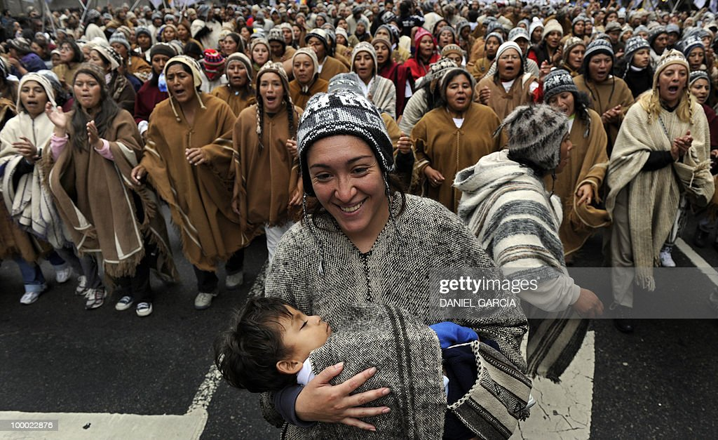A mother carries her son as thousands of demonstrators dance and sing as they participate in the National Indigenous March that arrived in the Plaza de Mayo in Buenos Aires after traveling some 2,000 km across the country, as part of the commemorations for the bicentennial of the Independence and to claim for a multicultural state that respects the rights of native peoples.