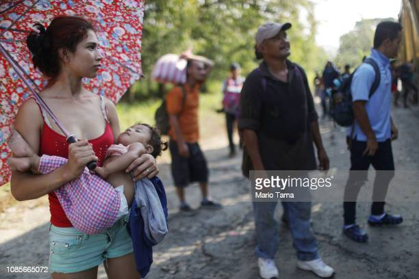 A mother carries her young daughter both part of a caravan of Central American migrants as they watch others board a truck they hoped to ride on...