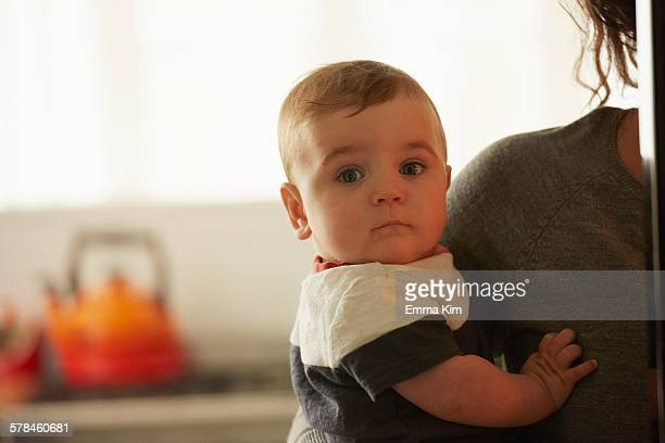 Mother carrying baby boy in kitchen