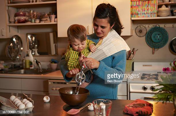 Mother carrying baby boy (12-17 months) whisking eggs in bowl