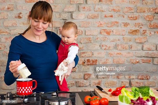 Mother carrying baby daughter whilst preparing lunch
