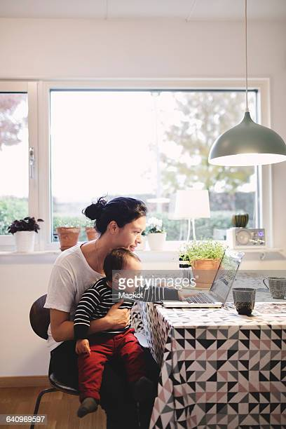 Mother carrying baby girl looking in laptop while sitting at kitchen