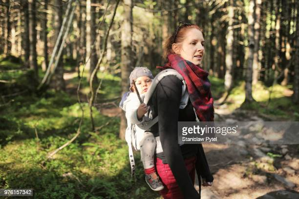 Mother carrying baby in asling in forest