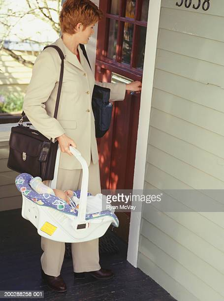 Mother carrying baby (3-6 months) in basket outside house